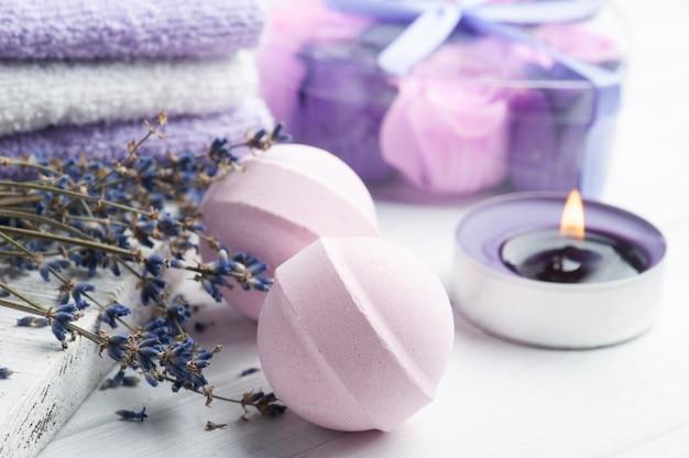 Bombe da bagno aromatiche rosa nella composizione spa con fiori di lavanda secca e asciugamani