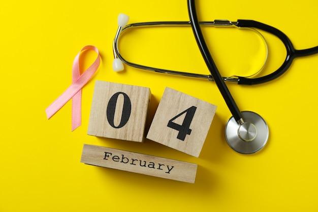 Nastro di consapevolezza rosa, stetoscopio e 4 febbraio su giallo
