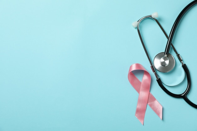 Nastro di consapevolezza rosa e stetoscopio su sfondo blu