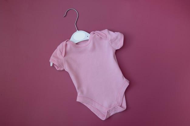 Vestiti rosa per bambini mock up per testo, immagine, logo. body per bebè in bianco