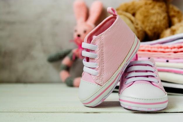 Scarpe da bambina rosa, vestiti per neonati e peluche. concetto di maternità, educazione o gravidanza con spazio di copia.