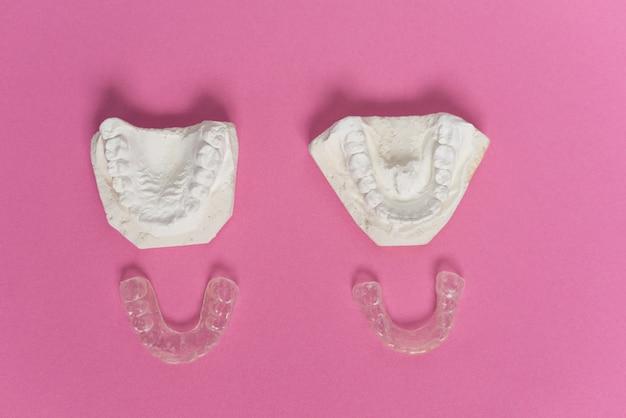 Su uno sfondo rosa giacciono dentiere di gesso