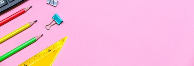 Sfondo rosa e forniture scolastiche multicolori tornano a scuola per gli scolari