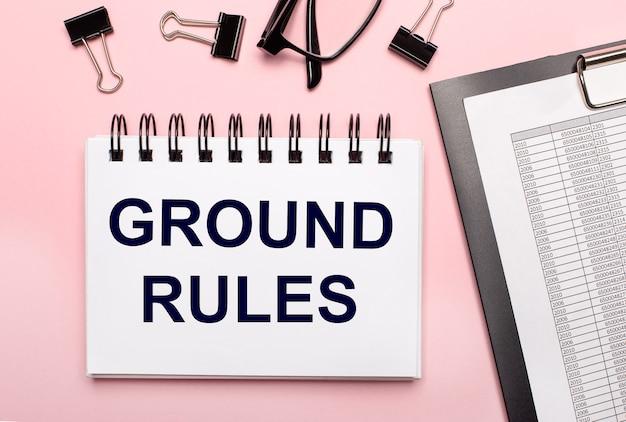 Su uno sfondo rosa, relazioni, graffette nere, occhiali e un quaderno bianco con il testo regole di base.