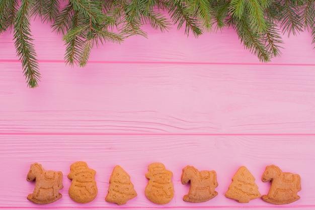 Sfondo rosa con rami di abete e biscotti di panpepato.