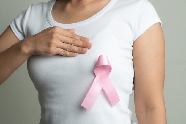 Nastro distintivo rosa sul petto della donna per sostenere la causa del cancro al seno