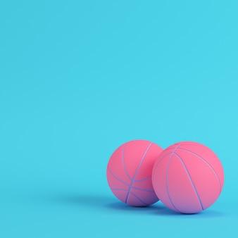 Palline da basket rosa su sfondo blu brillante