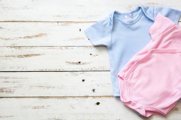 Pagliaccetto rosa e blu del bambino su fondo di legno bianco con lo spazio della copia