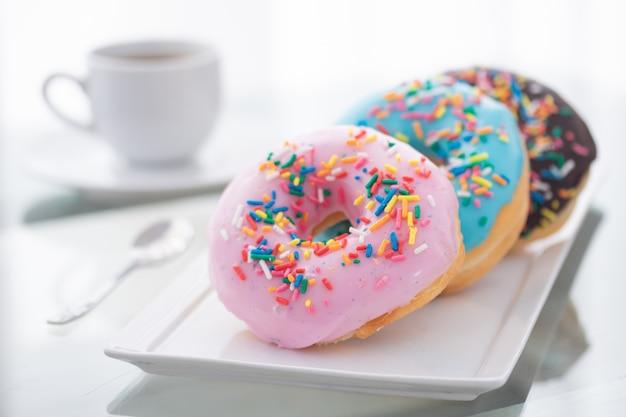 Ciambelle rosa, blu e cioccolato spruzza su un piatto bianco e una tazza di caffè