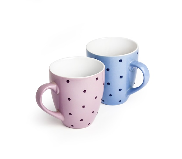 Tazze punteggiate rosa e blu isolate su superficie bianca con il percorso di residuo della potatura meccanica. copia spazio