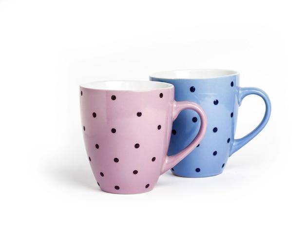 Tazze punteggiate rosa e blu isolate su superficie bianca con lo spazio della copia