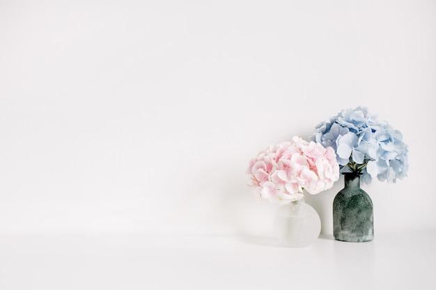 Mazzi di fiori di ortensie rosa e blu su superficie bianca