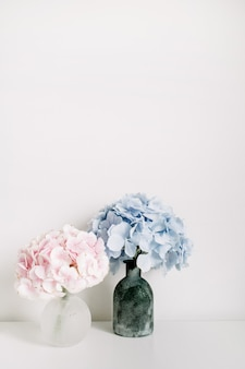 Mazzi di fiori di ortensie pastello rosa e blu su superficie bianca