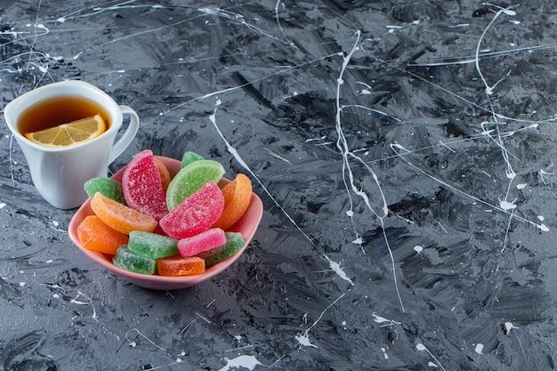 Ciotola rosa di marmellate colorate con una tazza di tè caldo sulla superficie di marmo.