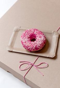 Torta rosa sulla scatola di consegna della carta con fiocco rosso su sfondo bianco, vista dall'alto.
