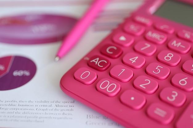 Calcolatrice rosa e penna sdraiata su documenti con grafici e diagrammi in primo piano