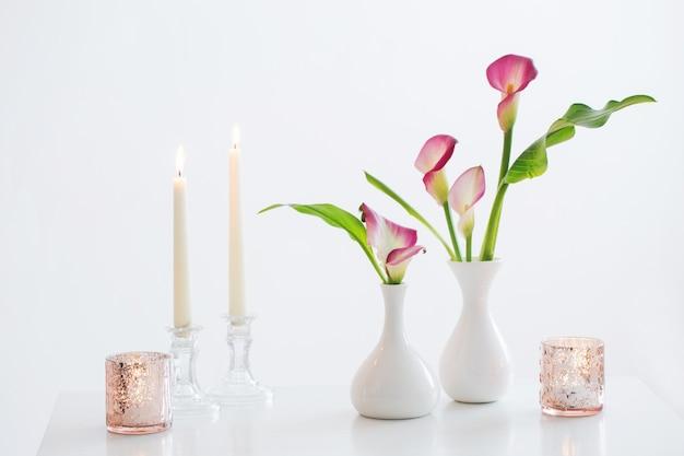 Giglio di calla rosa in vaso e candele accese su bianco