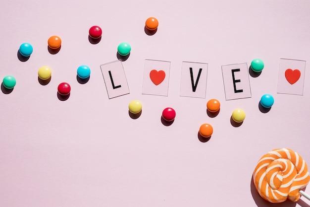 Caramelle rosa, lecca-lecca e gelatine con il testo dell'amore