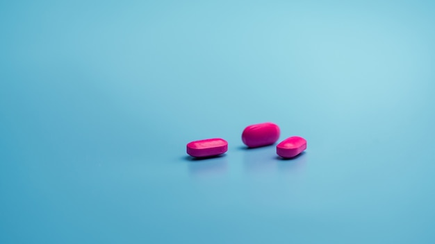 Pillole di capsule rosa su sfondo blu. industria farmaceutica. salute e medicina.