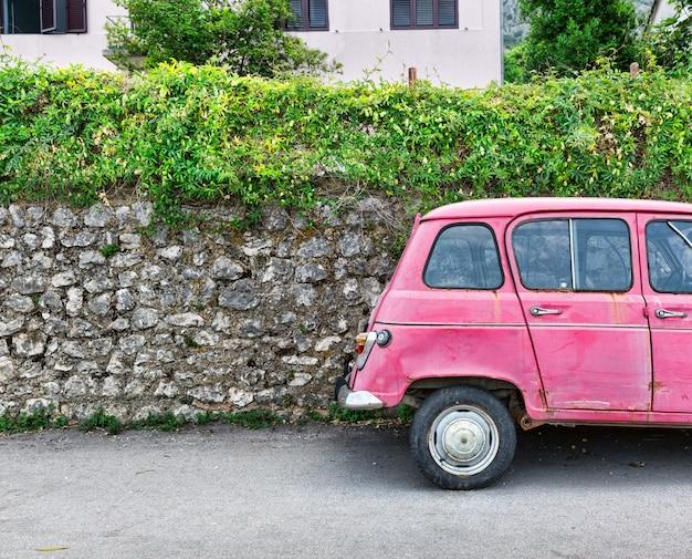 Automobile rosa vicino a un vecchio muro di mattoni