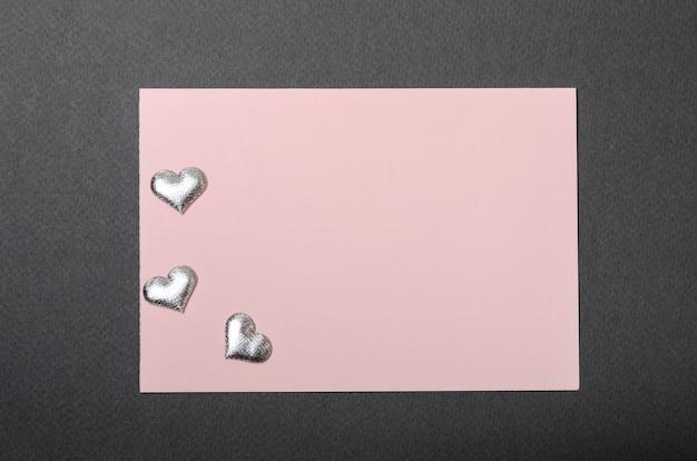 Carta rosa e cuori argentati su una parte superiore nera