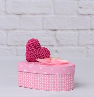 Scatola di cartone rosa a forma di cuore su sfondo bianco. sfondo festivo