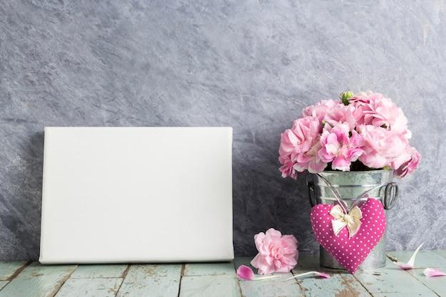 Fiore di garofano rosa in secchio di zinco con cuore di tessuto e cornice di tela bianca su vecchio legno