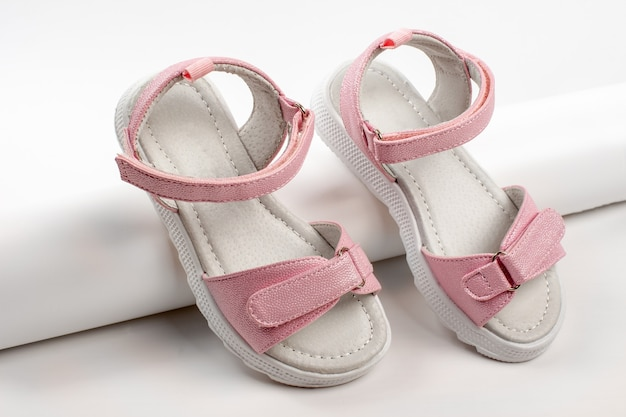 Sandali rosa per bambini in pelle lucida con chiusure in velcro suole piatte bianche isolate su...