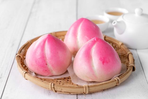 Il cibo cinese rosa del panino di compleanno della pesca ha chiamato lo shoutao della pesca di longevità sul fondo bianco della tavola.