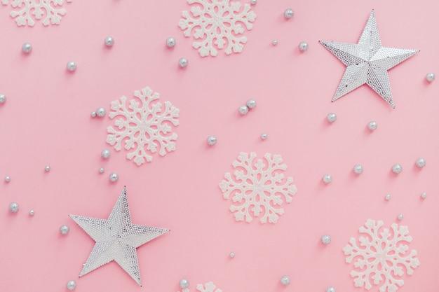 Sfondo rosa di natale stelle lucenti fiocchi di neve e bolle