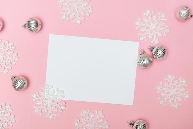 Sfondo di natale rosa con palline di decorazione di fiocchi di neve e vuoto vuoto per il testo laici copia spazio piatto