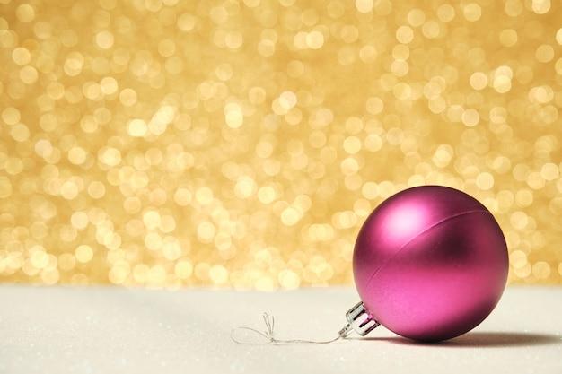 Sfera di natale rosa su superficie bianca lucida con sfondo dorato non focalizzato lucido