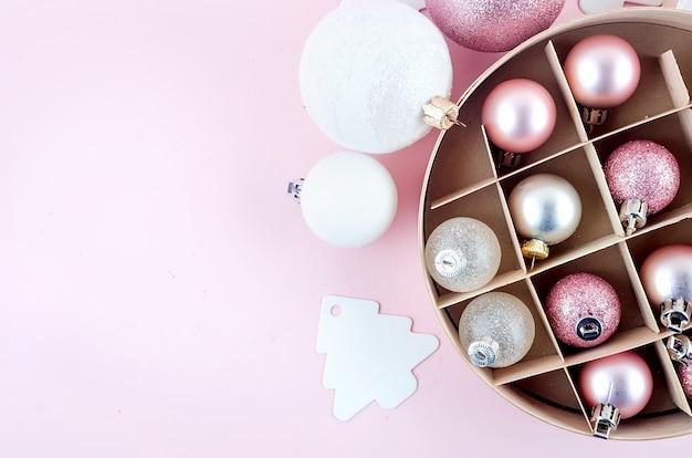Palle di natale rosa in scatola rotonda di legno su sfondo rosa pastello. luce dura, ombra.