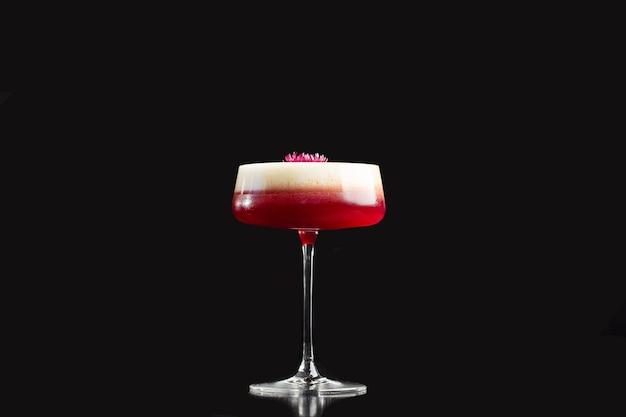 Pink clover club cocktail in coupe glass con strato di schiuma e decorazione floreale isolata