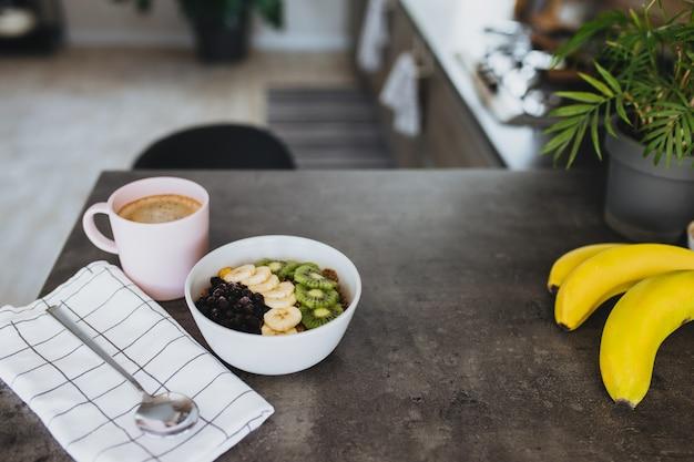 Tazza di caffè rosa, ciotola con kiwi e banana tritati di frutti tropicali, mirtilli, cucchiaio sul bancone del bar in elegante cucina loft.