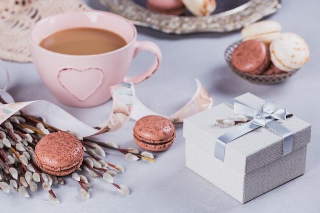 Tazza da caffè rosa con dolci amaretti francesi pastello