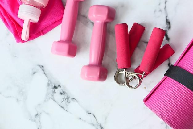 Manubri di colore rosa, tappetino per esercizi e bottiglia d'acqua su sfondo bianco.