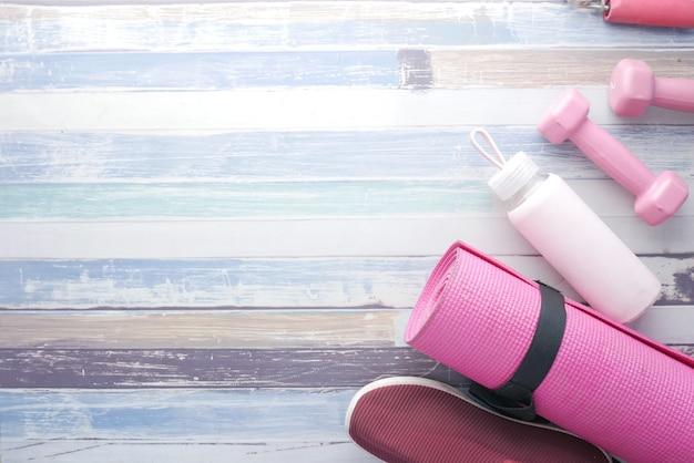 Tappetino per esercizi con manubri di colore rosa e bottiglia d'acqua su legno