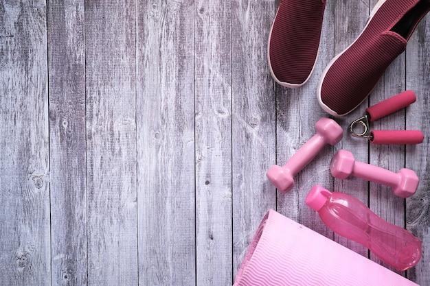 Manubrio di colore rosa, scarpa e bottiglia su fondo in legno