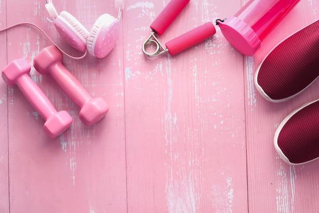 Dumbbell, scarpa e cuffia rosa di colore su fondo rosa