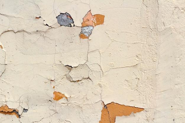 Muro di cemento rosa con graffi e danni