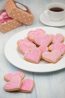 Biscotti rosa a forma di cuore su un piatto e una tazza di tè e scatole regalo il giorno di san valentino