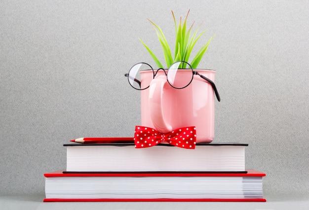 Tazza rosa sotto una pila di libri.
