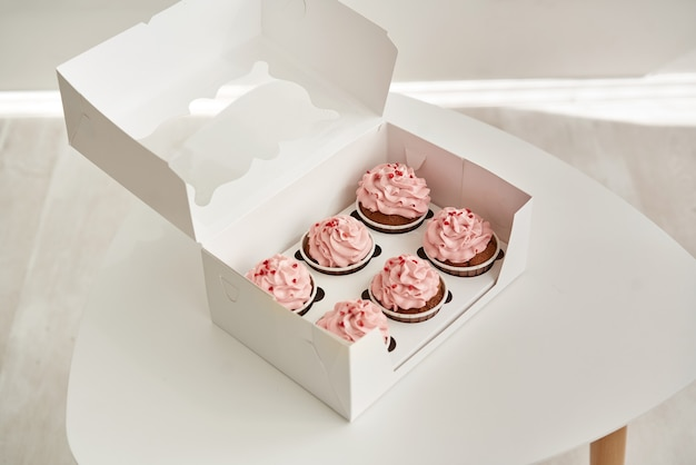 Cupcakes rosa in una confezione regalo bianca su un tavolo bianco