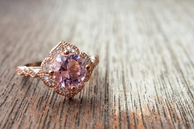 Anello con diamante rosa sul tavolo di legno
