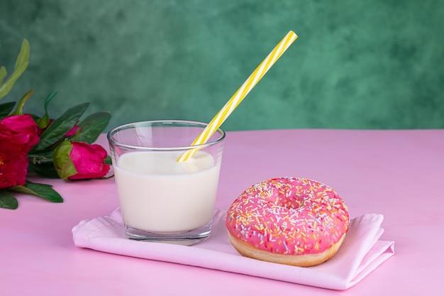Ciambella rosa con un bicchiere di latte su una superficie rosa