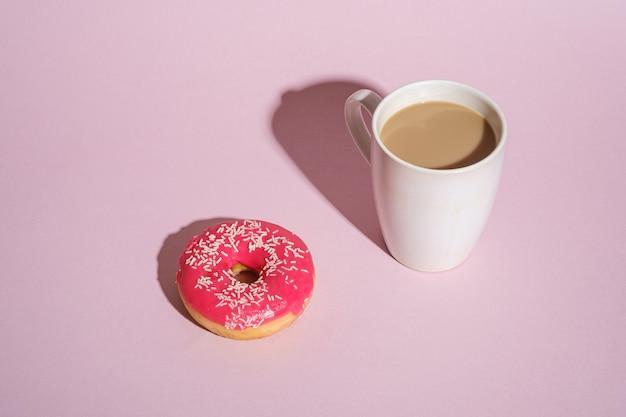 Ciambella rosa con un pizzico vicino alla tazza di caffè, dolce glassato cibo da dessert e bevanda calda su sfondo rosa minimo, angolo vista spazio di copia
