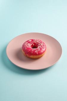 Ciambella rosa con un pizzico sul piatto rosa, dolce cibo da dessert glassato sul minimo blu, angolo di visione