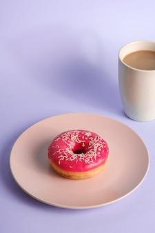 Ciambella rosa con un pizzico sulla piastra vicino alla tazza di caffè, dolce glassato cibo da dessert e bevanda calda su sfondo blu minimo, angolo di visione
