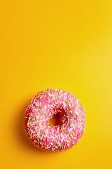 Ciambella rosa sullo spazio giallo della copia di vista superiore